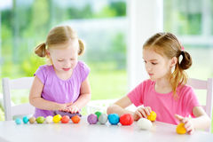 Two cute little sisters having fun together with modeling clay at a daycare. Creative kids molding at home. Children play with pla. Two cute little sisters Stock Image