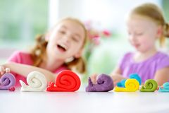 Two cute little sisters having fun together with modeling clay at a daycare. Creative kids molding at home. Children play with pla. Two cute little sisters Stock Photography