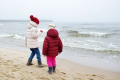 Two cute little sisters having fun together at winter beach on cold winter day. Kids playing by the ocean. Winter activities for children stock image