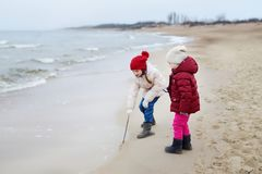 Two cute little sisters having fun together at winter beach on cold winter day. Kids playing by the ocean. Stock Photos