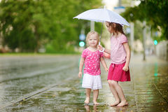 Two cute little sisters having fun under a rain Royalty Free Stock Photos