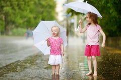 Two cute little sisters having fun under a rain Stock Photo