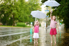 Two cute little sisters having fun under a rain Royalty Free Stock Photo