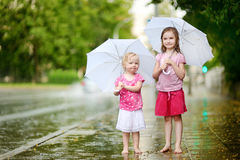 Two cute little sisters having fun under a rain Stock Images