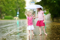 Two cute little sisters having fun under a rain Stock Photo