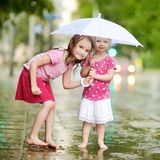 Two cute little sisters having fun under a rain Royalty Free Stock Images