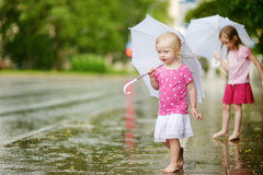 Two cute little sisters having fun under a rain Royalty Free Stock Photography