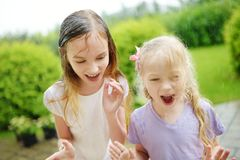 Two cute little sisters having fun under warm summer rain. Siblings playing together outdoors stock photos