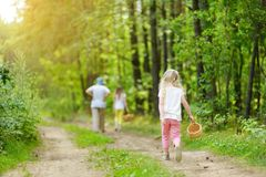 Two cute little sisters hiking in a forest with their grandmother on beautiful summer day. Family time in summer royalty free stock photo