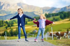 Two cute little sisters hiking in Seiser Alm, the largest high altitude Alpine meadow in Europe Royalty Free Stock Images