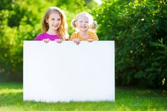 Two cute little sisters holding big blank whiteboard Stock Photography