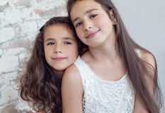 Two cute little sisters huddled together Royalty Free Stock Photo