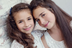 Two cute little sisters huddled together Royalty Free Stock Photos