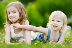 Two cute little sisters laying in the grass Stock Images