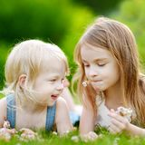 Two cute little sisters laying in the grass. Two cute little sisters having fun while laying in the grass on a sunny summer day stock photography