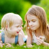 Two cute little sisters laying in the grass Stock Photo