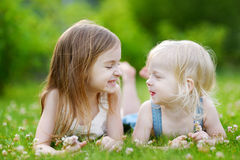 Two cute little sisters laying in the grass Royalty Free Stock Photos