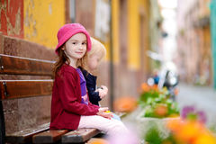 Two cute little sisters outdoors. Two cute little sisters sitting on a bench outdoors on hot and sunny summer day royalty free stock photos