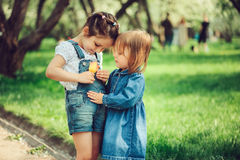 Two cute little sisters playing with flower on the walk in summer Stock Photo