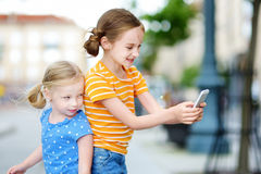 Two cute little sisters playing outdoor mobile game on their smart phones Stock Image