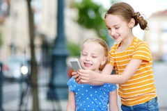 Two cute little sisters playing outdoor mobile game on their smart phones Stock Photos