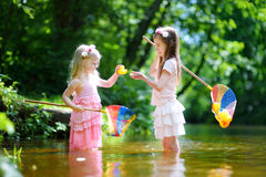 Two cute little sisters playing in a river catching rubber ducks with their scoop-nets Stock Image