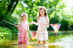 Two cute little sisters playing in a river catching rubber ducks with their scoop-nets Royalty Free Stock Photography