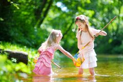 Two cute little sisters playing in a river catching rubber ducks with their scoop-nets Royalty Free Stock Image