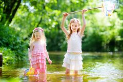 Two cute little sisters playing in a river catching rubber ducks with their scoop-nets Royalty Free Stock Photos