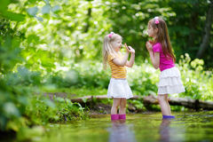 Two cute little sisters playing in a river wearing raining boots Royalty Free Stock Image