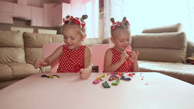 Two cute little sisters, with pleasure together with colorful modeling. Creative children at home. Children play with. Plasticine or dough stock video footage