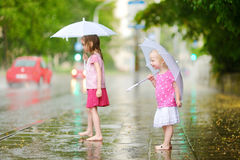 Two cute little sisters on a rainy summer day Stock Image