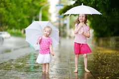 Two cute little sisters on a rainy summer day Royalty Free Stock Images
