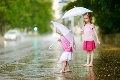 Two cute little sisters on a rainy summer day Stock Photo