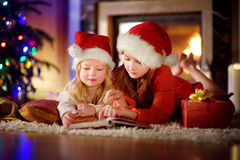 Two cute little sisters reading a story book together under a Christmas tree Stock Images