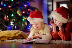 Two cute little sisters reading a story book together under a Christmas tree. On Christmas eve at home Stock Photos