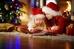 Two cute little sisters reading a story book together under a Christmas tree. Two cute little sisters reading a story book together under a  tree on  eve at home Royalty Free Stock Photo