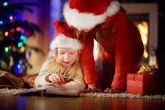 Two cute little sisters reading a story book together under a Christmas tree. Two cute little sisters reading a story book together under a  tree on  eve at home Royalty Free Stock Photography
