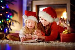 Two cute little sisters reading a story book together under a Christmas tree. Two cute little sisters reading a story book together under a  tree on  eve at home Stock Photo