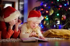 Two cute little sisters reading a story book together under a Christmas tree. Two cute little sisters reading a story book together under a  tree on  eve at home Royalty Free Stock Photos