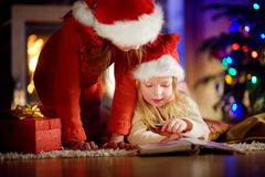 Two cute little sisters reading a story book together under a Christmas tree. On Christmas eve at home Royalty Free Stock Image
