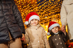 Two cute little sisters in the red Santa's hats Stock Photos