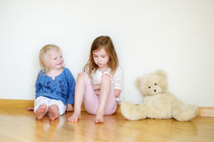 Two cute little sisters sitting on a floor Royalty Free Stock Photo