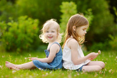 Two cute little sisters sitting on the grass Stock Photography