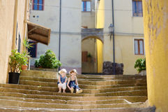 Two cute little sisters sitting on stairs Royalty Free Stock Photos