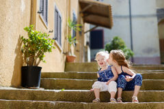 Two cute little sisters sitting on stairs Royalty Free Stock Photo