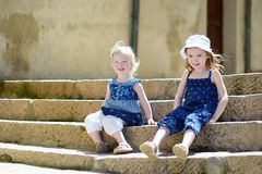 Two cute little sisters sitting on stairs Royalty Free Stock Image