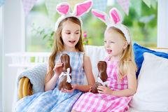 Two cute little sisters wearing bunny ears eating chocolate Easter rabbits Royalty Free Stock Images