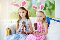 Two cute little sisters wearing bunny ears eating chocolate Easter rabbits. Kids playing egg hunt on Easter. Stock Photo