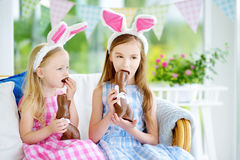 Two cute little sisters wearing bunny ears eating chocolate Easter rabbits. Kids playing egg hunt on Easter. Stock Photos